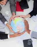 Multi-ethnic business people holding a globe. Close-up of multi-ethnic business people holding a terrestrial globe in the office Stock Images