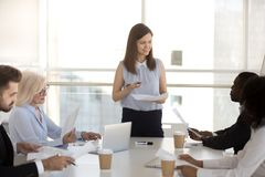 Multi-ethnic business people sitting on the briefing. Businesswoman make presentation for colleagues company staff, answer questions feel confident teach explain royalty free stock photography
