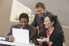Multi Ethnic Business People Smiling While Looking At Laptop Stock Images