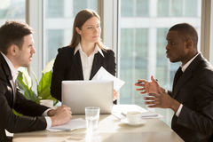 Multi-ethnic business team discussing project idea sitting at of. Multi-ethnic business team discussing project or idea sitting at office desk, partners working Stock Photo