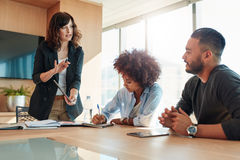 Multi ethnic business team discussing project. Young businesswoman showing something to her colleagues during a meeting in conference room. Multi ethnic business stock photos