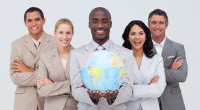Multi-ethnic business team holding a terrestrial g. Lobe in office stock photo