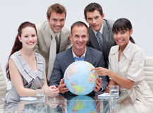 Multi-ethnic business team holding a terrestrial g. Lobe in office royalty free stock photos