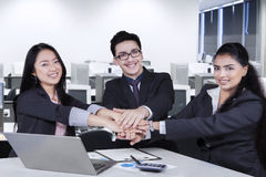 Multi ethnic business team joining their arms Stock Photo