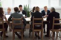 Multi-ethnic business team sitting at conference table, negotiat. Serious multi-ethnic business people team sitting at conference table, senior executives Royalty Free Stock Photos