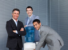 Multi-ethnic business team at water cooler Stock Image