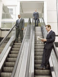 Multi Ethnic Businessmen Standing On Escalator In Office Stock Photography