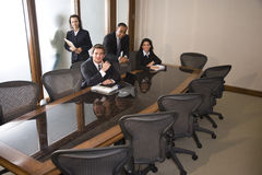 Multi-ethnic businesspeople in boardroom stock images