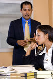 Multi-ethnic businesspeople in office boardroom. Young African-American female office worker reading papers in boardroom with middle-aged Hispanic businessman Stock Photo