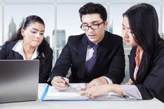 Multi ethnic businessteam signing a document Stock Photos