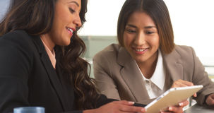 Multi-ethnic businesswomen reviewing information on tablet. In the office stock photo