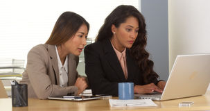 Multi-ethnic businesswomen working on laptop. In the office Royalty Free Stock Images