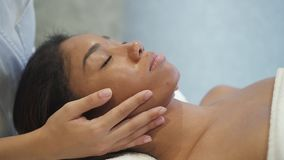 Multi ethnic calm young woman is getting medical face massage from professional hand. Skin beauty and facial care for attractive hispanic female in slow motion stock video footage