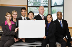 Multi-ethnic co-workers posing with blank sign royalty free stock images