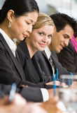 Multi-ethnic co-workers sitting in a row Royalty Free Stock Image