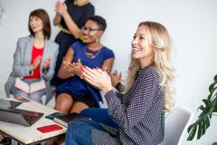 Multiethnic female team applauding during business seminar in conference hall royalty free stock photos