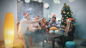 Multi-ethnic company in Santa hats blowing party whistle and making cheers in smoke. They sit on sofa near the xmas tree with skyscrapers in the background stock video