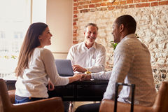 A multi ethnic couple checking in at a boutique hotel Royalty Free Stock Images