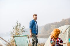 Friends during the outdoor recreation. Multi ethnic couple of friends dressed casually talking during the outdoor recreation with tent near the lake Stock Photo