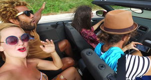 Multi ethnic couple having fun riding in back seat of convertible with friends. Young mixed race couple having fun riding in the back seat of convertible with stock video