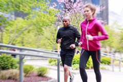 Multi-ethnic Couple Jogging In Urban Setting Royalty Free Stock Images