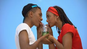 Multi-ethnic couple in love drinking glass of fresh cocktail through two straws. Stock footage stock video footage