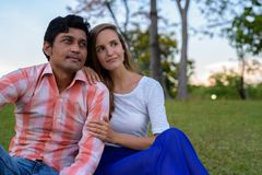 Multi ethnic couple sitting and thinking on the meadow in love a. T peaceful green park royalty free stock photography