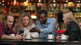 Multi-ethnic couples sitting in a cafe show photos to each other and laugh. Multi-ethnic couples sitting in a cafe show photos to each other and laugh stock video