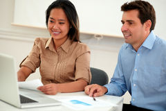 Multi ethnic coworkers couple working on documents Royalty Free Stock Photos