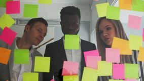 Multi ethnic creative team conducts brainstorming all their ideas are pasted on colored stickers on the glass wall. African American male and blonde team up in stock footage