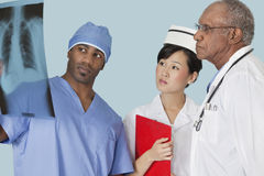 Multi ethnic doctors examining x-ray report over light blue background Royalty Free Stock Photo
