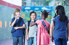 Multi ethnic elementary classroom kids greeting each other in th Royalty Free Stock Image