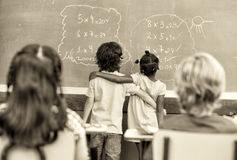 Multi ethnic elementary students embraced learning math at chalk Royalty Free Stock Photos