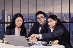 Multi ethnic employees discussing in office. Portrait of three multi ethnic entrepreneurs discussing business plan and strategy with laptop in the office Royalty Free Stock Image