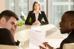 Multi-ethnic employers impressed by job seeker resume, focus on Stock Photography