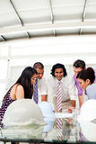 Multi-ethnic engineers reviewing blueprints Royalty Free Stock Images