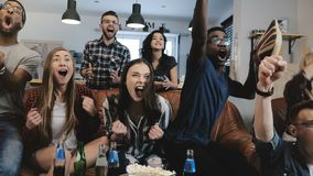 Multi-ethnic fans go crazy celebrating goal on TV. Passionate football supporters scream with arms raised 4K slow motion. Close up. Euphoria. Football fever Royalty Free Stock Photos