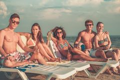 Multi ethnic friends with drinks relaxing on a beach Royalty Free Stock Photos