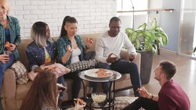 Multi-ethnic friends eat pizza at home and talk stock video footage