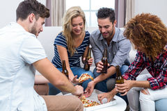 Multi-ethnic friends enjoying beer and pizza Stock Photography