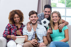 Multi-ethnic friends enjoying beer while watching soccer match. Portrait of multi-ethnic friends enjoying beer while watching soccer match at home Royalty Free Stock Photography