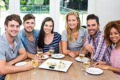 Multi-ethnic friends enjoying wine and sushi on table Royalty Free Stock Photography