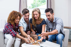 Multi-ethnic friends holding beer while eating pizza Royalty Free Stock Photography