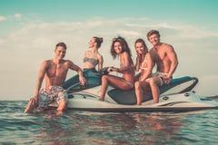 Multi ethnic friends on a jet ski Stock Photos