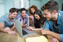 Multi-ethnic friends laughing and looking in laptop Stock Photo