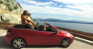 Multi ethnic friends partying in red convertible parked on side of coastal road. Multi ethnic friends partying in red convertible car parked on the side of stock video