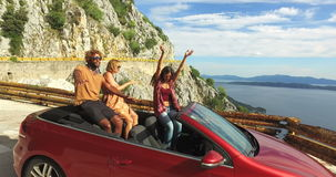 Multi ethnic friends partying in red convertible parked on side of coastal road. Three multi ethnic friends partying in red convertible car parked on the side of stock footage