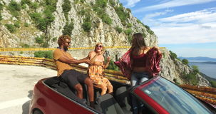 Multi ethnic friends partying in red convertible parked on side of coastal road. Three multi ethnic friends partying in red convertible car parked on the side of stock video footage