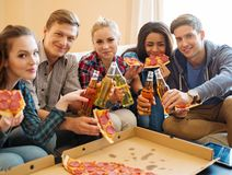 Multi ethnic friends with pizza and bottles of drink Stock Image