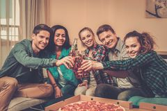 Multi-ethnic friends with pizza and bottles of drink Royalty Free Stock Photography